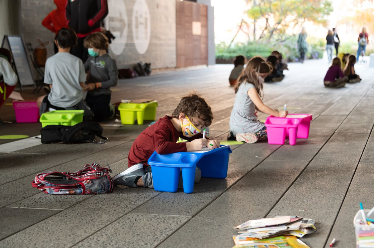 A little boy in a red shirt and protective face mask colors on a small blue object, as other students also work in the background on the High Line Park in New York City.