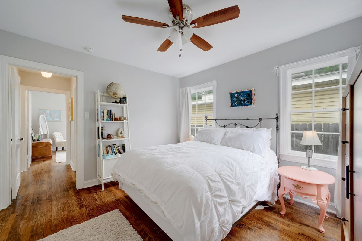 A bed with a white comforter is pushed against a wall with two windows. There is a ceiling fan with wood blades and pink bedside tables.