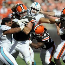 Sep 8, 2013; Cleveland, OH, USA; Cleveland Browns quarterback Brandon Weeden (3) has his face mask grabbed by Miami Dolphins defensive end Jared Odrick (98) as Cleveland Browns tackle Joe Thomas (73) and Cleveland Browns running back Trent Richardson (33)