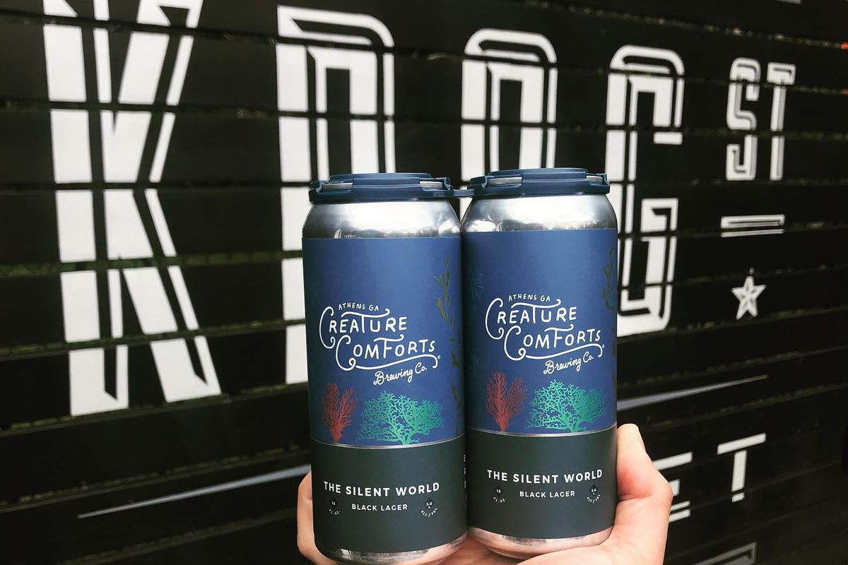 """A hand with a tattooed arm holding two cans of Creature Comfort """"The Silent World"""" black lager in front of the black painted wall with the white Krog Street Market logo on it"""