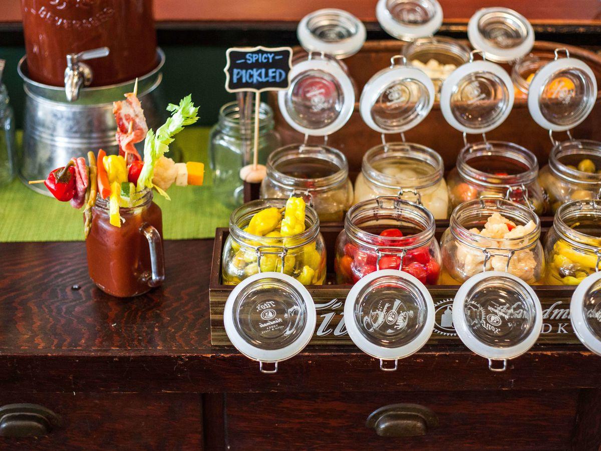 A bloody mary in a mason jar next to a selection of other containers displaying a variety of garnishes.