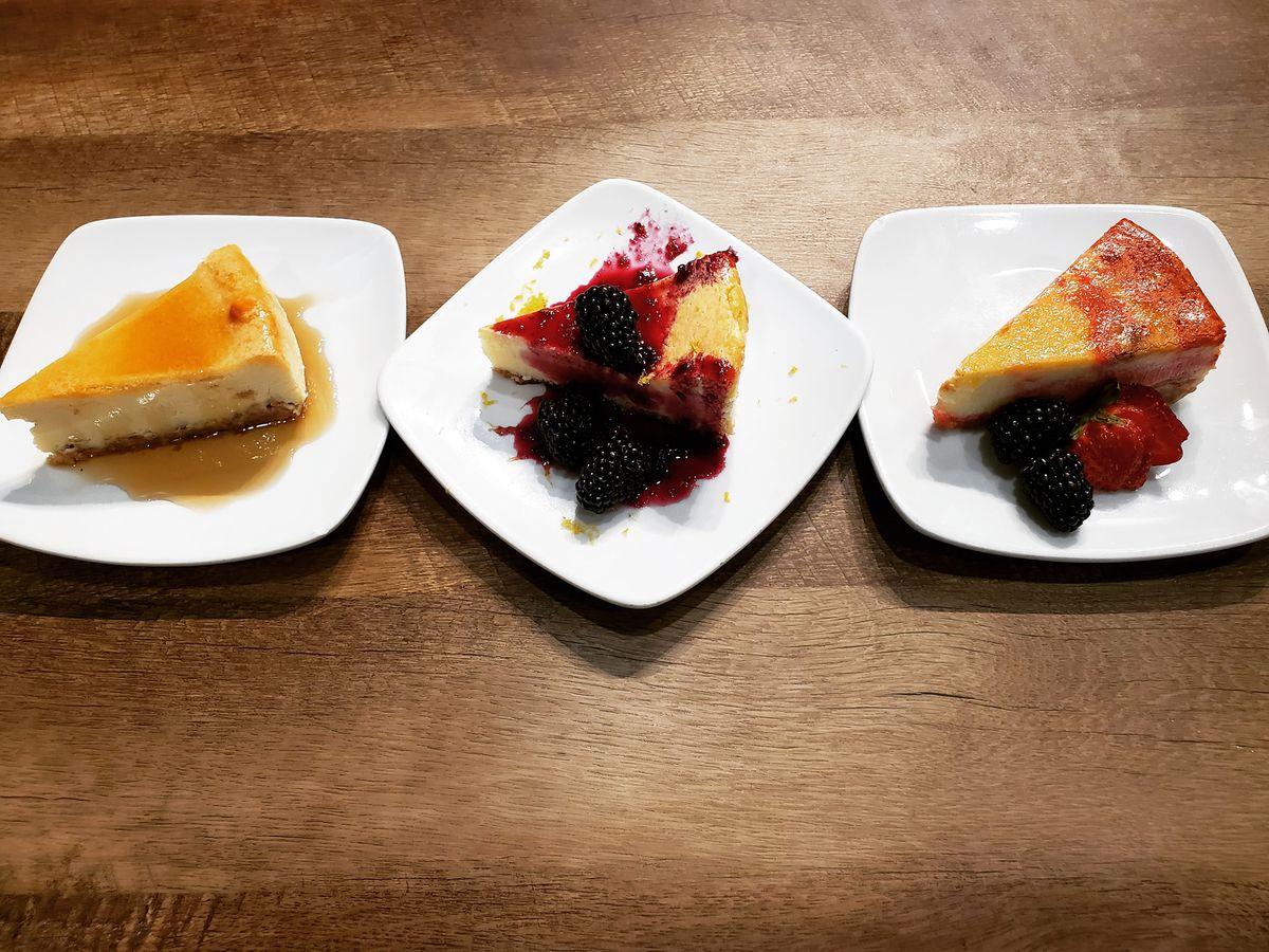 Three slices of cheesecake on white plates.