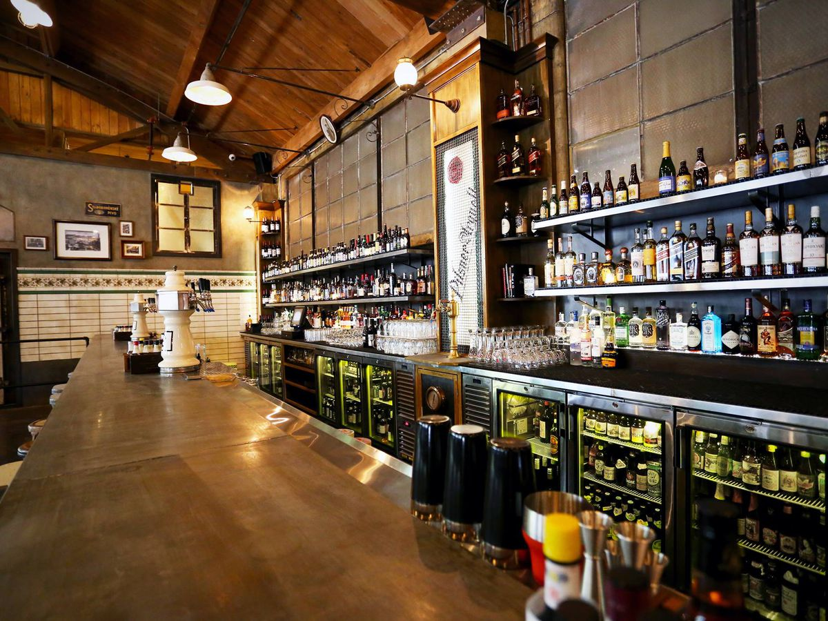 A view of a long bar and shelves of bottles at Queen Anne Beerhall.