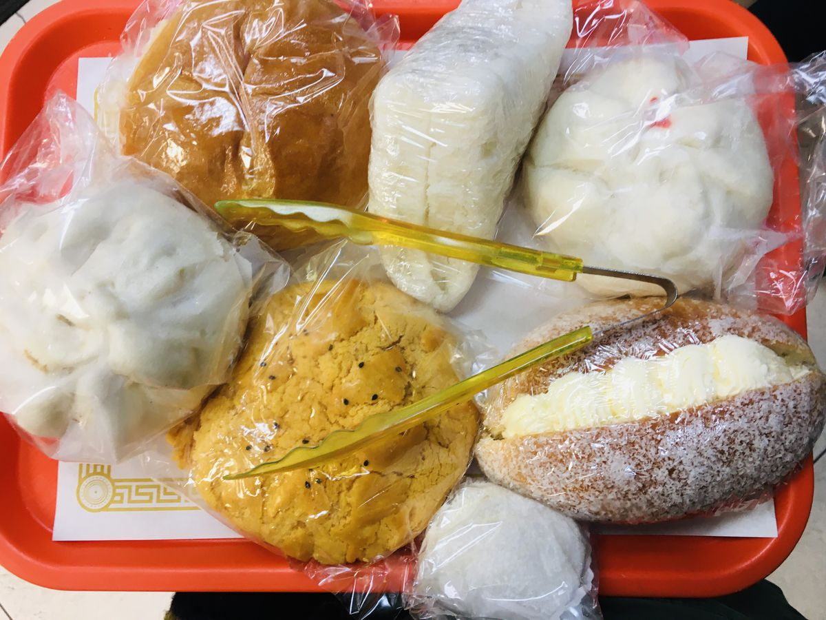 An assortment of Chinese buns and pastries on a red tray with yellow tongs on top.