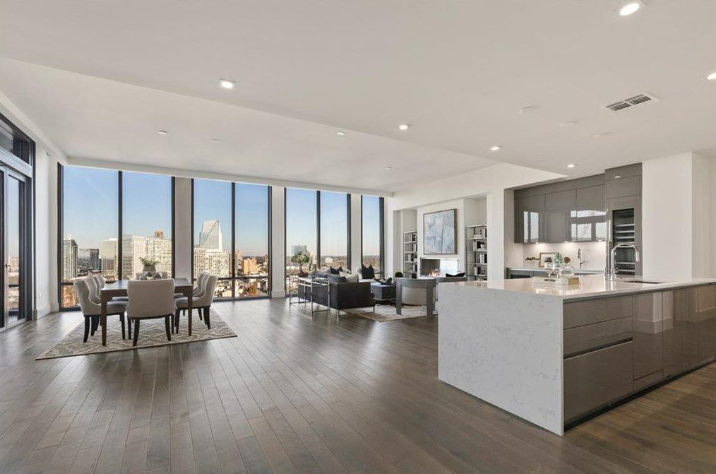 A large white condo room with huge windows and a kitchen at right.