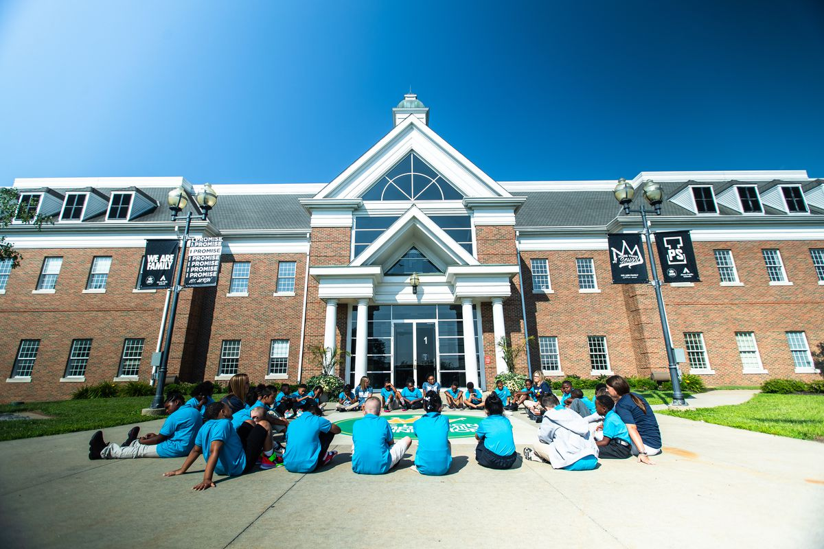 A circle of students in blue t-shirts sit outside the entrance to a school