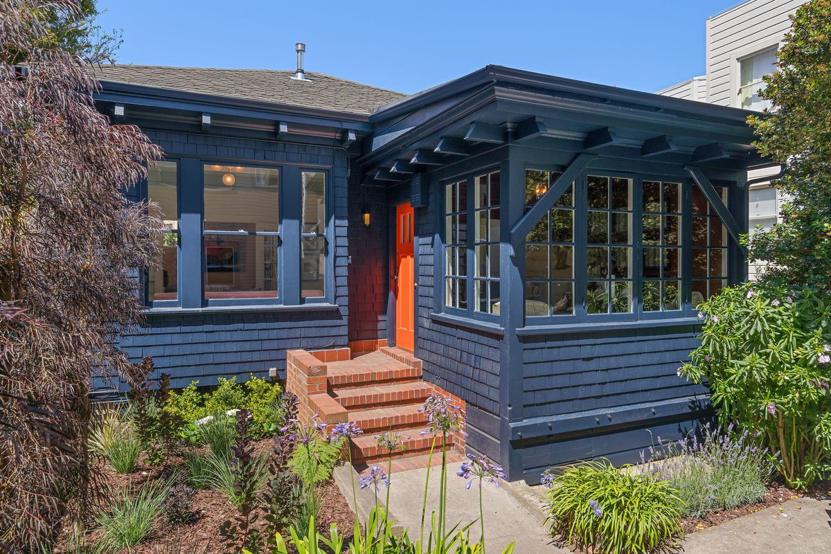 Cottage-like home with brick steps, navy blue facade, orange door, pitched roof, and windows galore.