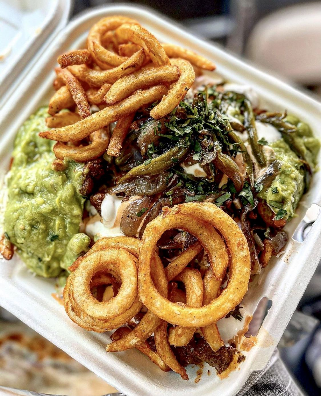 A box of curly fries topped with grilled onions, cilantro, and jalapenos
