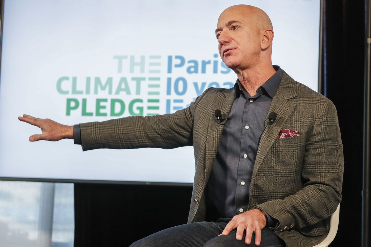 """Amazon CEO Jeff Bezos sitting down onstage and speaking with his right arm extended at his side in front of a """"Climate Pledge"""" logo."""