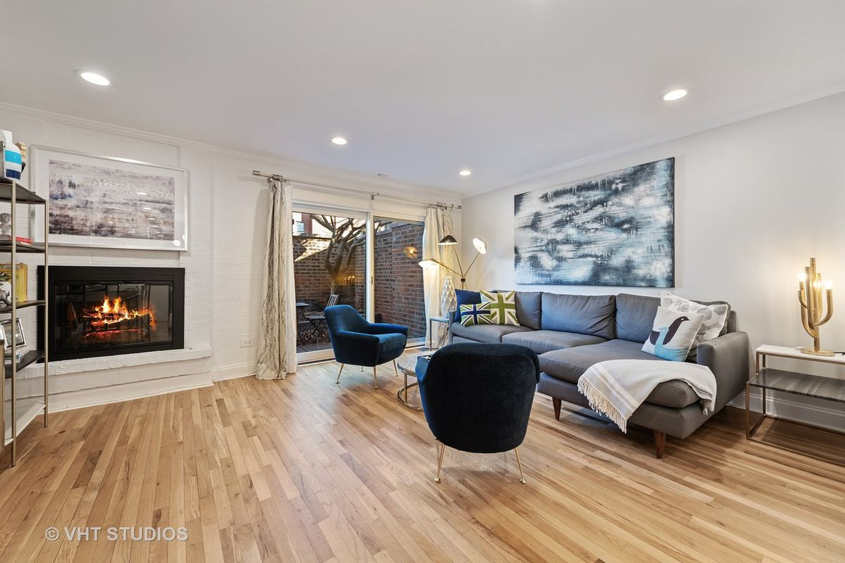 The living room features a couch, two chairs, a wood burning fireplace, a hardwood floor, and a brick-paved patio.