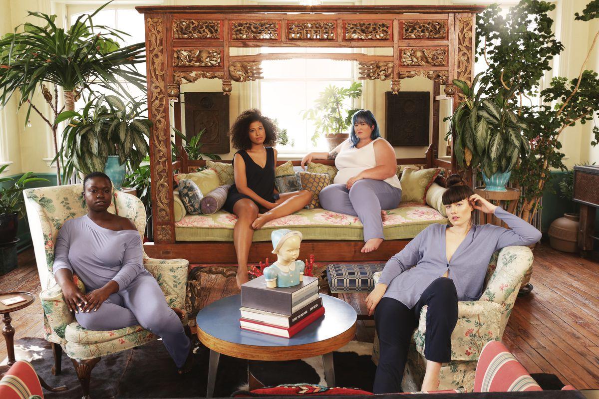 Four women wearing loungewear in an ornate living room