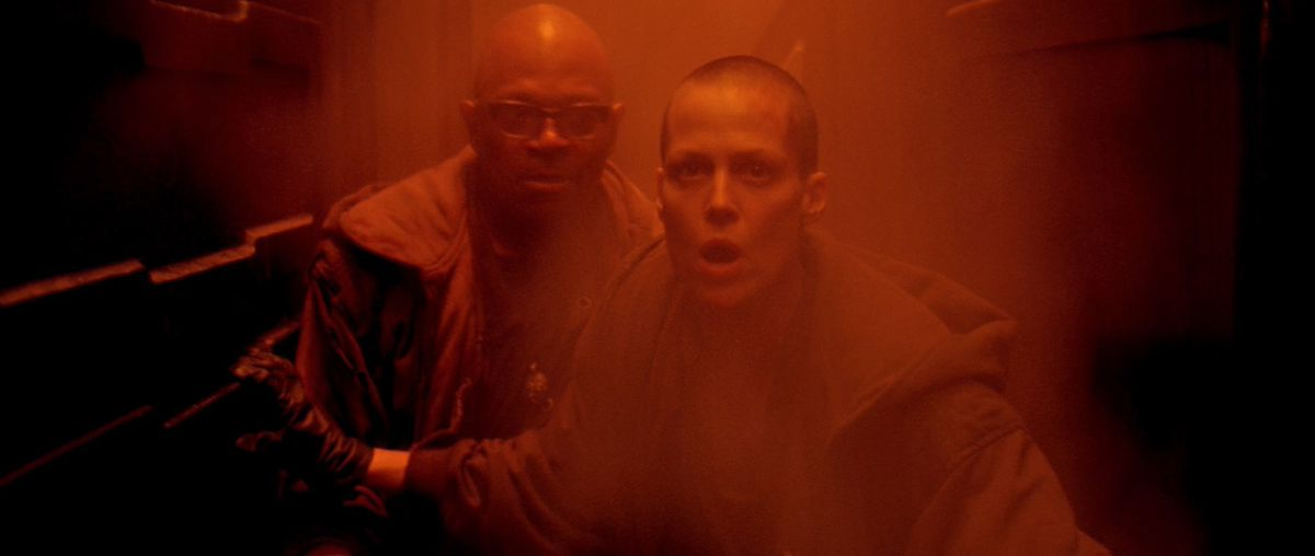 Leonard (Charles S. Dutton) and Ripley (Sigourney Weaver) race through a red-lit hall in Alien 3