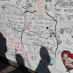People cast shadows as they read a message board placed near Grenfell Tower in London, Saturday, June 17, 2017. Police Commander Stuart Cundy said Saturday it will take weeks or longer to recover and identify all the dead in the public housing block that was devastated by a fire early Wednesday.
