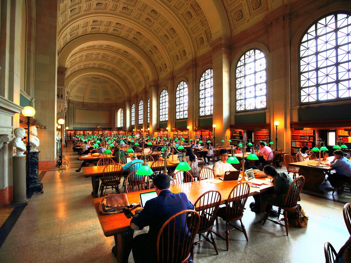 A long, capacious room with several rows of tables and people sitting quietly at those tables.