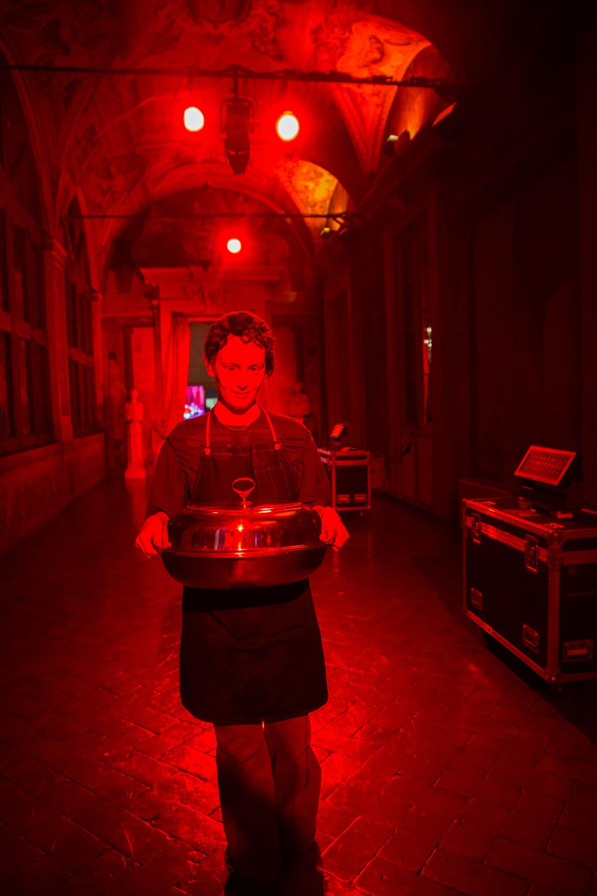 Person walks down a red hallway carrying a large covered pot.