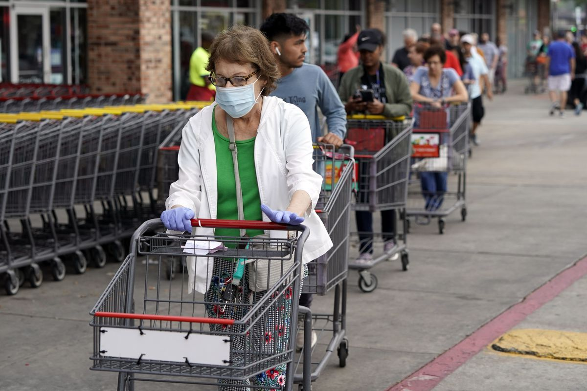 A white woman with brown and gray hair wears a mask and gloves as she enters an H-E-B grocery after waiting in line with more than 150 people. She's pushing a grocery basket.
