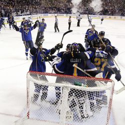 St. Louis Blues players celebrate with goaltender Brian Elliott as time expires against the San Jose Sharks during the third period in Game 5 of an NHL Stanley Cup first-round hockey playoff series, Saturday, April 21, 2012, in St. Louis. The Blues won 3-1 and won the series 4-1.
