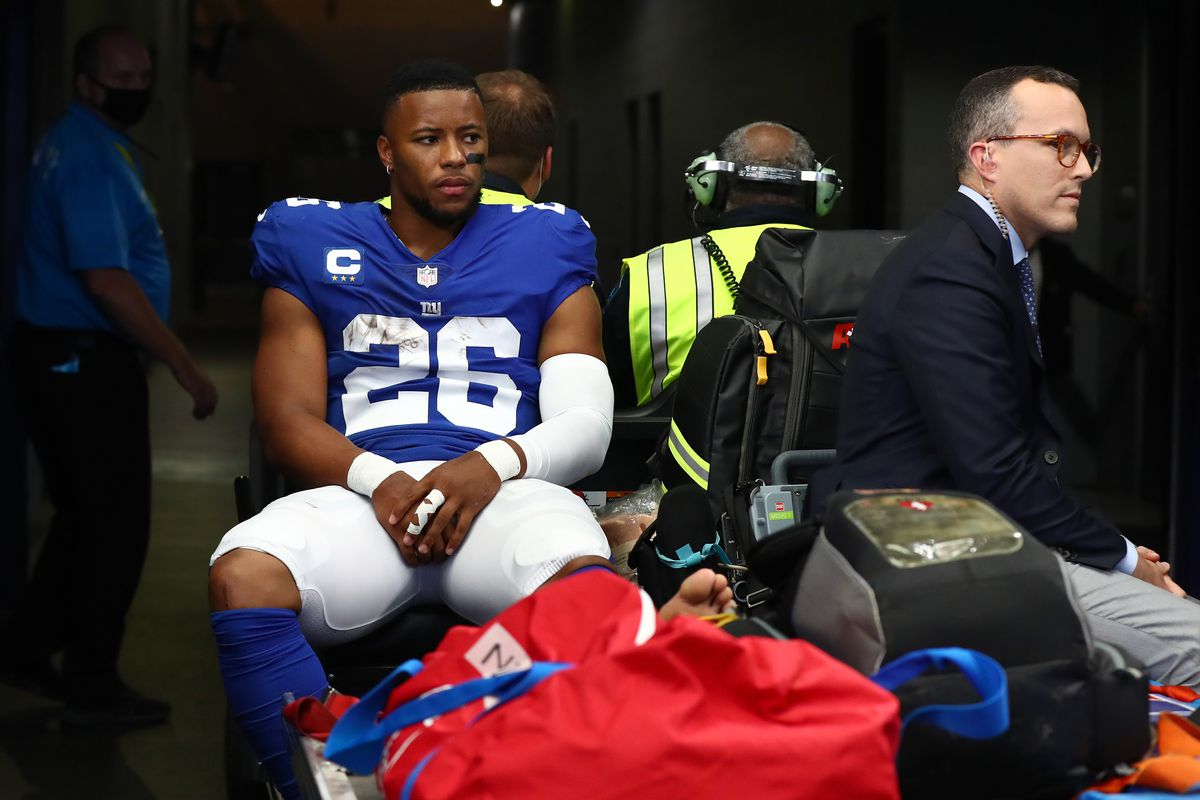 New York Giants running back Saquon Barkley heads to the locker room on a medical cart in the first half during the game against the Dallas Cowboys at AT&T Stadium.