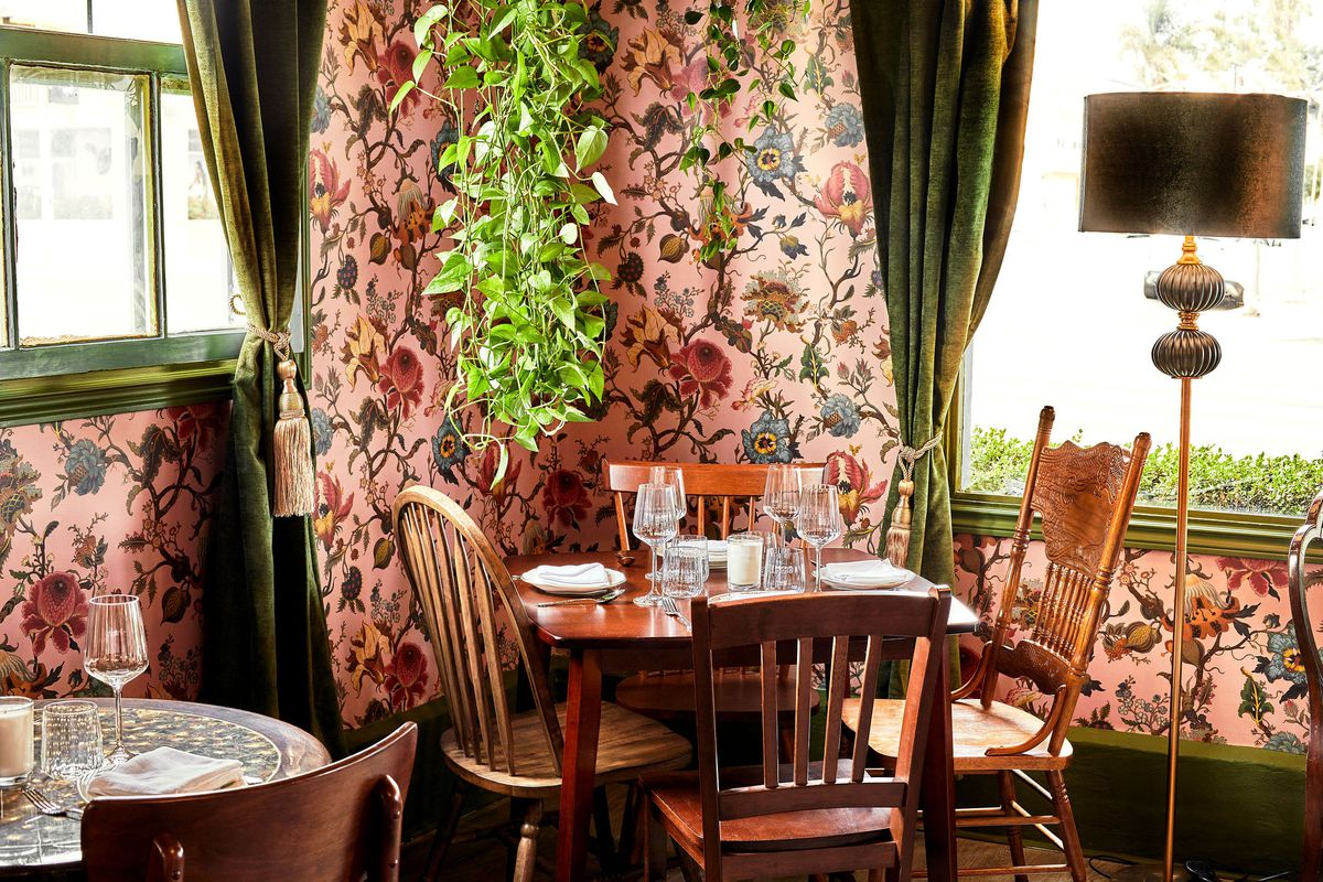 Dining room at Cobi's in Santa Monica with mismatched wooden chairs, pink floral wallpaper, and a hanging plant.