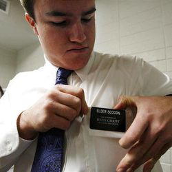 Elder John Scoggin puts on his name tag in preparation to leave the Provo Missionary Training Center of The Church of Jesus Christ of Latter-day Saints in Provo, Utah Tuesday, Feb. 15, 2011.