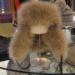 Eugenia Kim Owen Hat in Beige<br />Eugenia Kim hats are simply fabulous! This insanely luxurious fox fur trooper hat features a ear flaps and black leather cord trim.<br />Originally $825, with 60% off $330