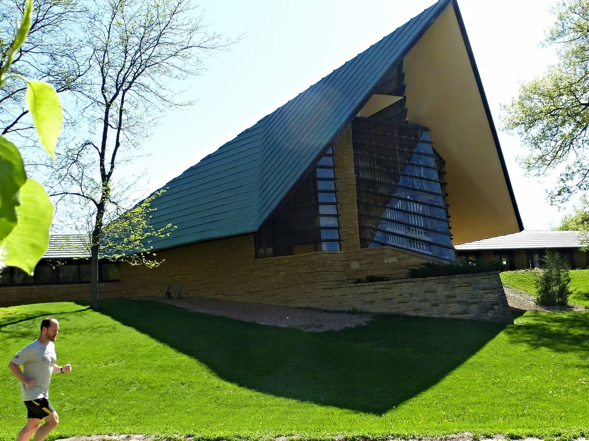 Unitarian Meeting House by Frank Lloyd Wright. There is a dark blue angled roof and a tan brick facade. There is a green grass lawn in front of the church.