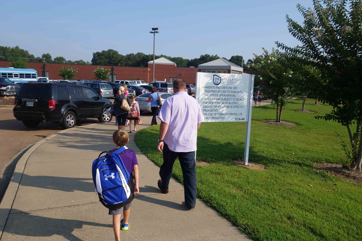 Hauling a backpack almost as big as himself, a student walks into Lakeland Elementary School on the first day of the 2014-15 school year. A resolution filed in the Tennessee General Assembly recommends that schools promote ways to avoid backpack-related injuries.