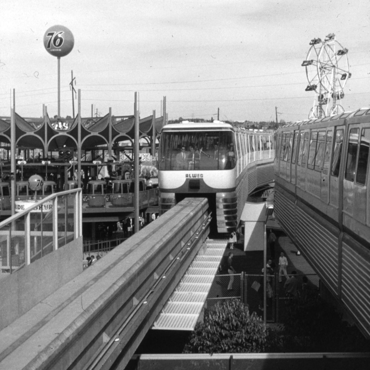 A monorail car leaves the World's Fair, with a Ferris wheel visible in the background