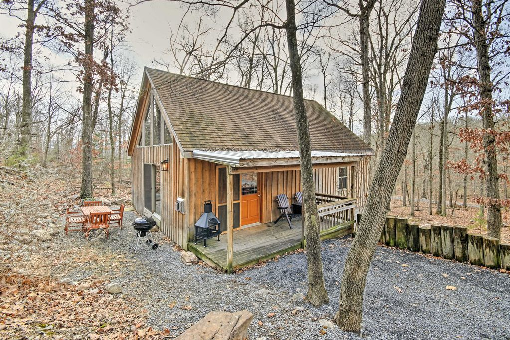 A wooden cabin with a front porch, stove, and Adirondack chairs sits in a forest with trees that have lost their leaves.
