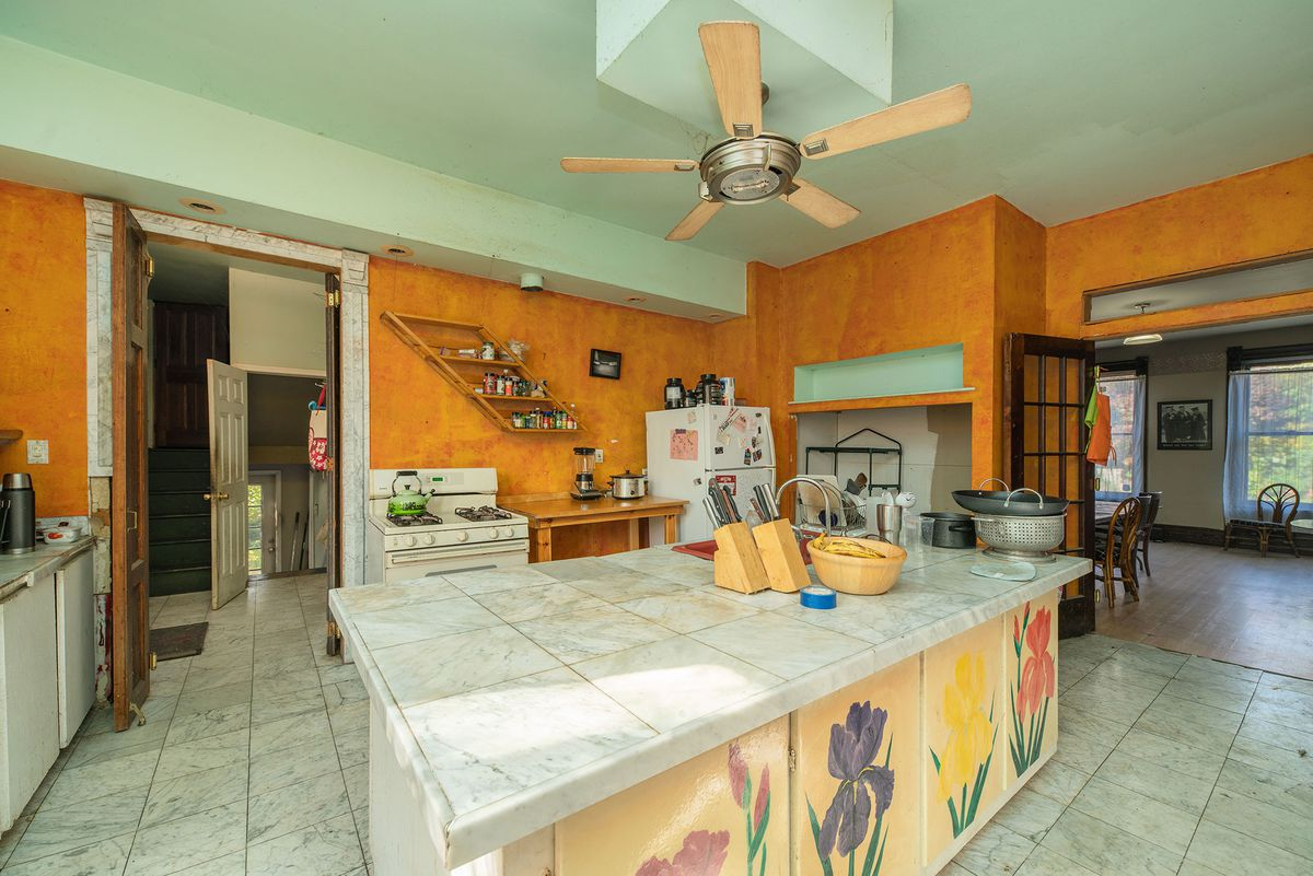 A huge kitchen with a large, rectangular white-tiled island.