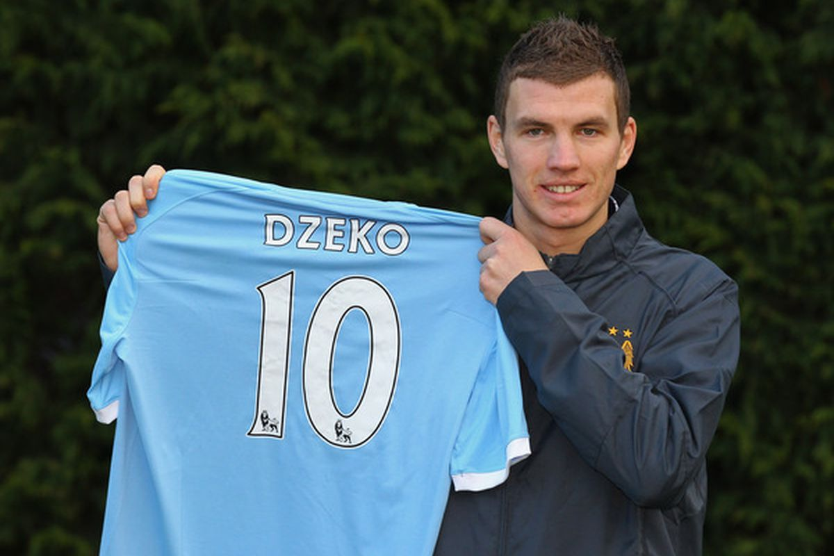 MANCHESTER ENGLAND - JANUARY 11:  Edin Dzeko the new signing for Manchester City poses with his new shirt during a photocall at the Carrington Training Complex on January 11 2011 in Manchester England.  (Photo by Alex Livesey/Getty Images)