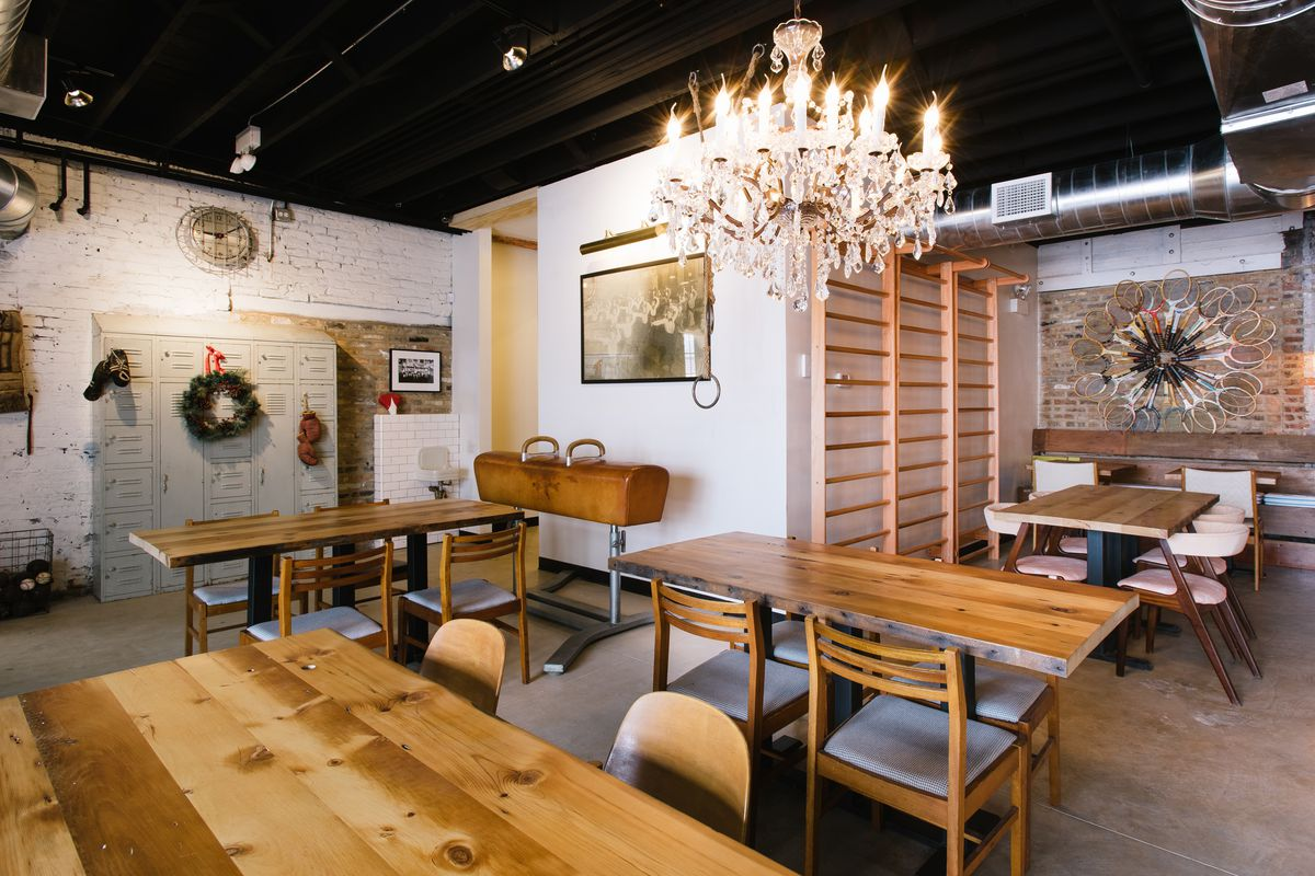 A white-walled room is filled with several four-top wooden tables. A chandelier hangs over head in the brightly-lit space, and art hangs on the walls.