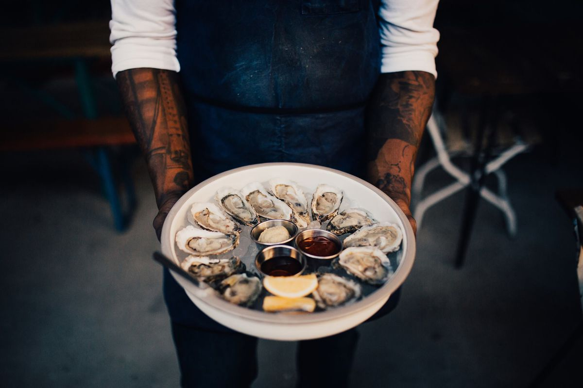 A man with tattoo sleeved arms hold a platter of raw oysters at WH Stiles Fish Camp
