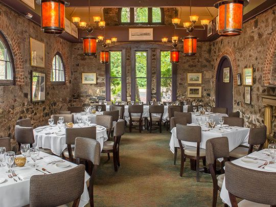 The stone-walled dining room at Gandy Dancer has four-top tables draped in white tablecloths.