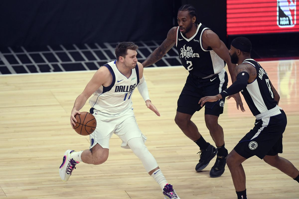 Luka Doncic of the Dallas Mavericks is double teamed by Kawhi Leonard of the Los Angeles Clippers and Marcus Morris Sr. of the Los Angeles Clippers during the first half of Game Seven of the Western Conference first round series at Staples Center on June 6, 2021 in Los Angeles, California.