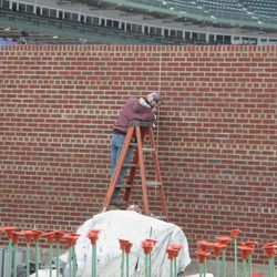 Contractor working on the new inner bleacher wall in the right-field corner -