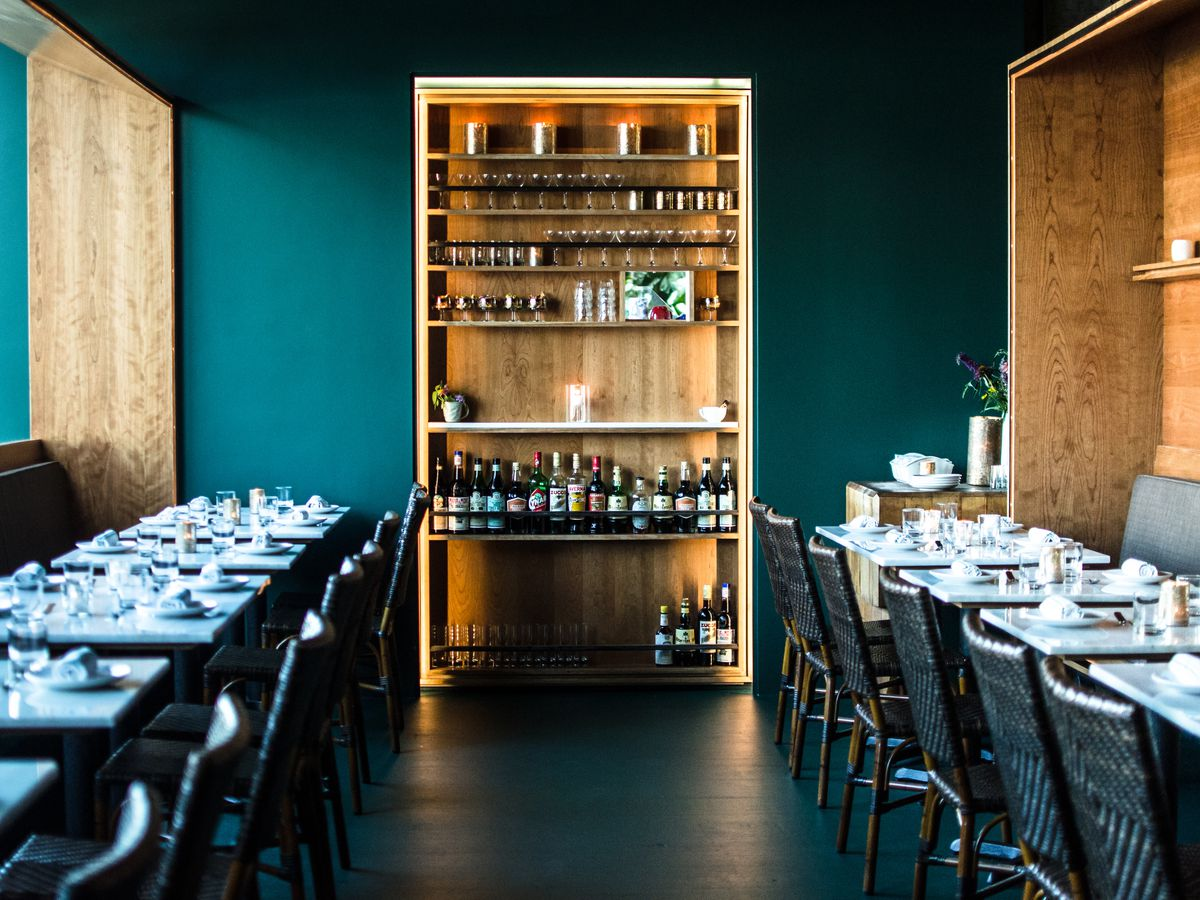 Interior of a small restaurant with dark teal walls and light wooden accents.