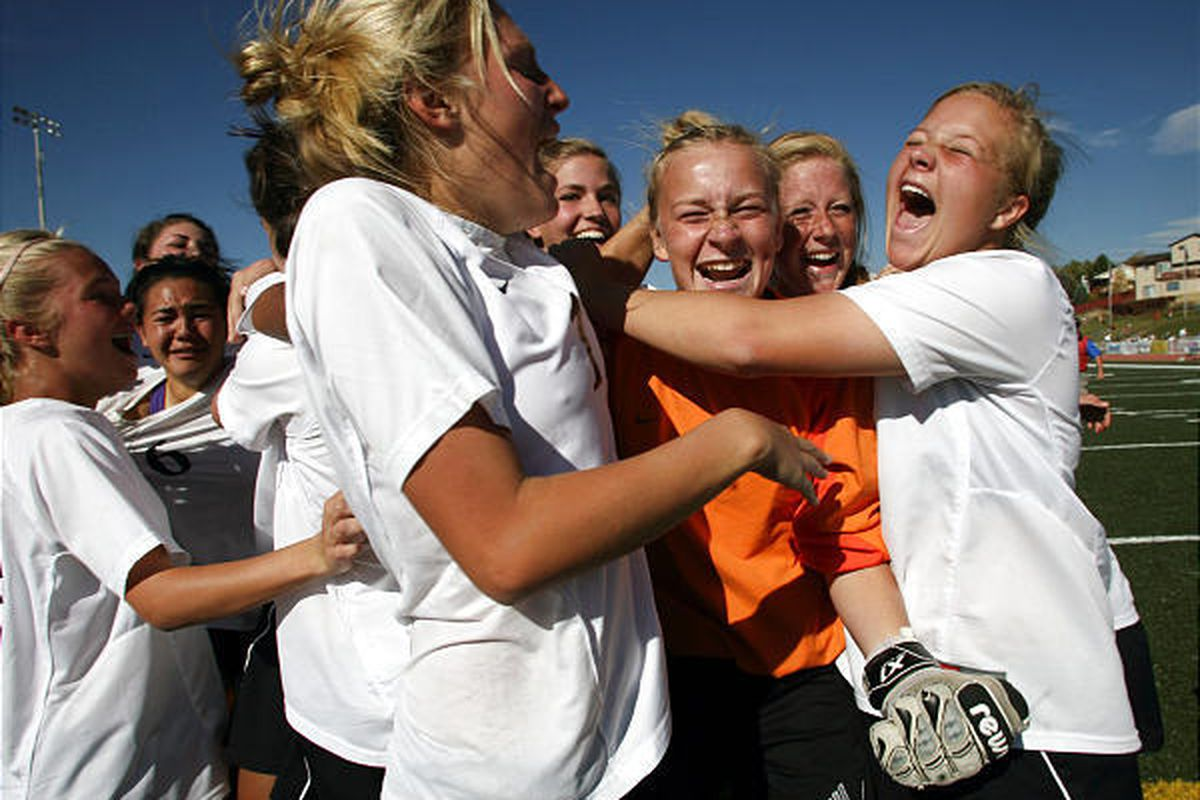 The Waterford girls soccer team surrounds goalkeeper Jeannie Woller (in orange) as they celebrate their 3A championship Saturday.