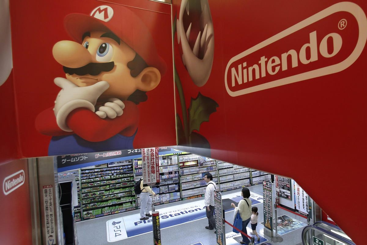FILE - In this May 7, 2014, file photo, shoppers walk under the logo of Nintendo and Super Mario characters at an electronics store in Tokyo. Nintendo announced July 14, 2016, that it was bringing back its classic Nintendo Entertainment System for fall 20