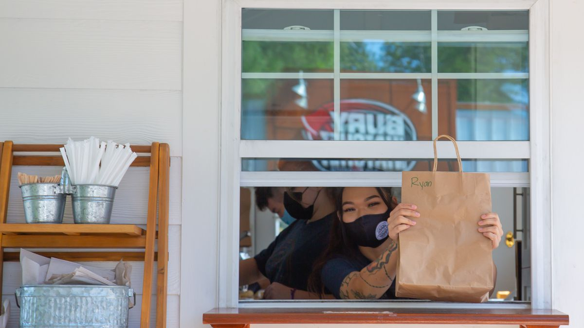 A woman of Asian descent in a black mask and tee shirt with tattooed arms handing a brown takeout bag through an open window. A wooden stand next to the window contains tins of straws, wooden coffee stirrers, and napkins