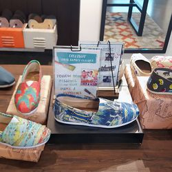 The shop offers TOMS's collection of slip-ons hand-painted by Haitian artists.