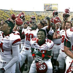 Utah's Sean Smith (4), Justin Taplin-Ross (33) and Dustin Hensel (65) celebrate as the University of Utah defeats then No. 24-ranked Michigan Wolverines, 25-23.