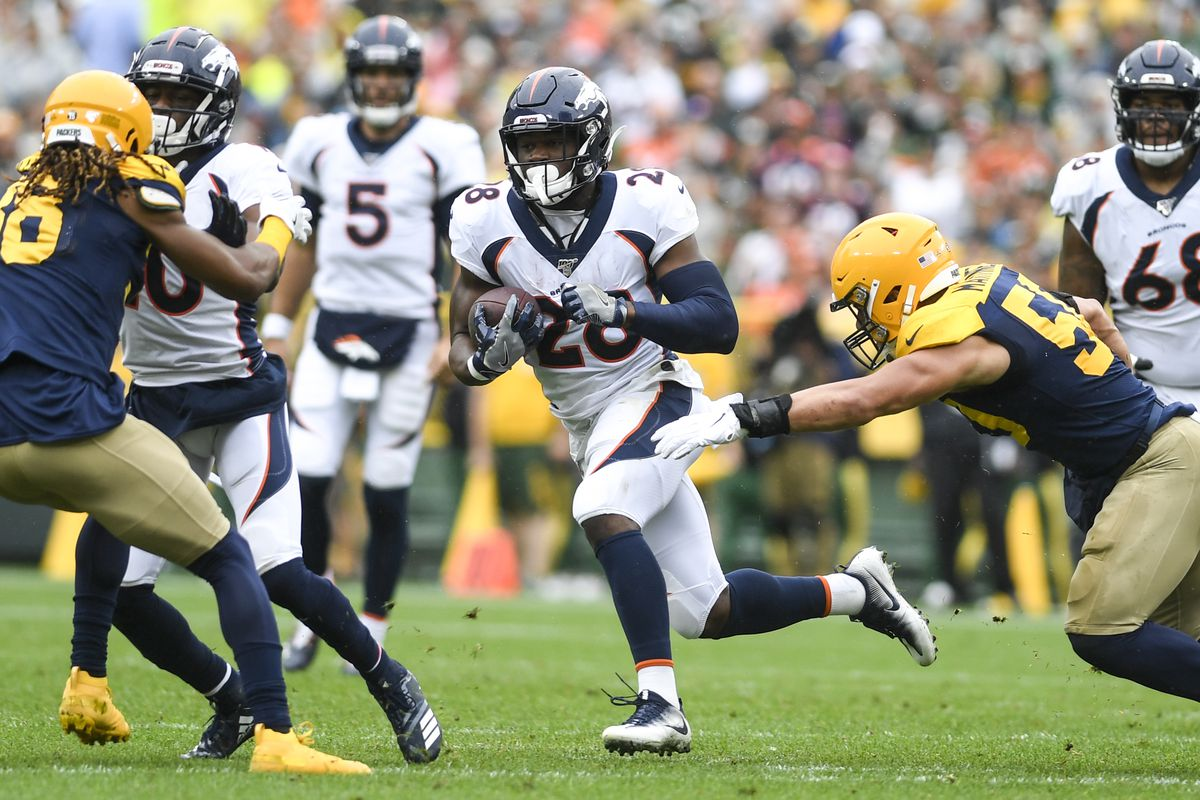 Royce Freeman of the Denver Broncos runs as Blake Martinez of the Green Bay Packers tries to get a hand on him during the first half on Sunday, September 22, 2019.
