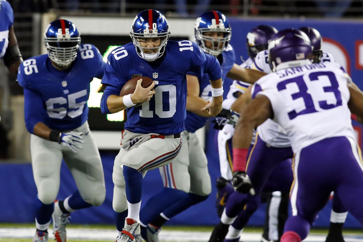Eli Manning runs for a first down in the first quarter Monday night.