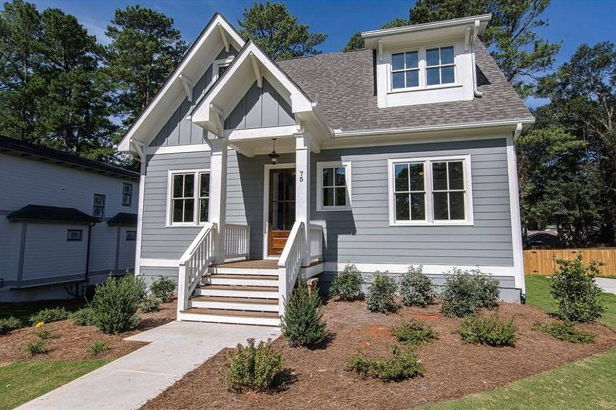 A gray house with white trim and a small porch.