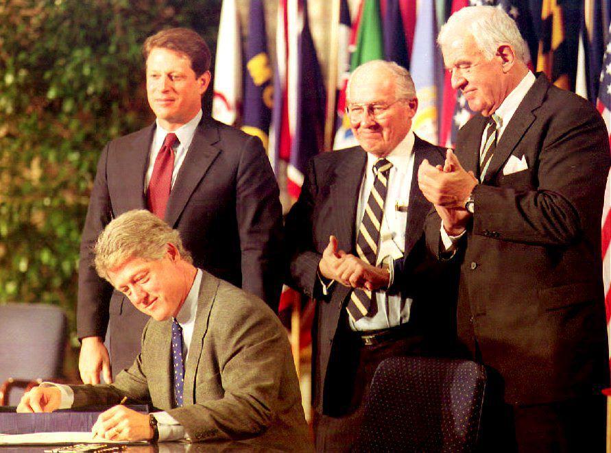 Bill Clinton signs NAFTA alongside Al Gore, Bob Michel, and Tom Foley.
