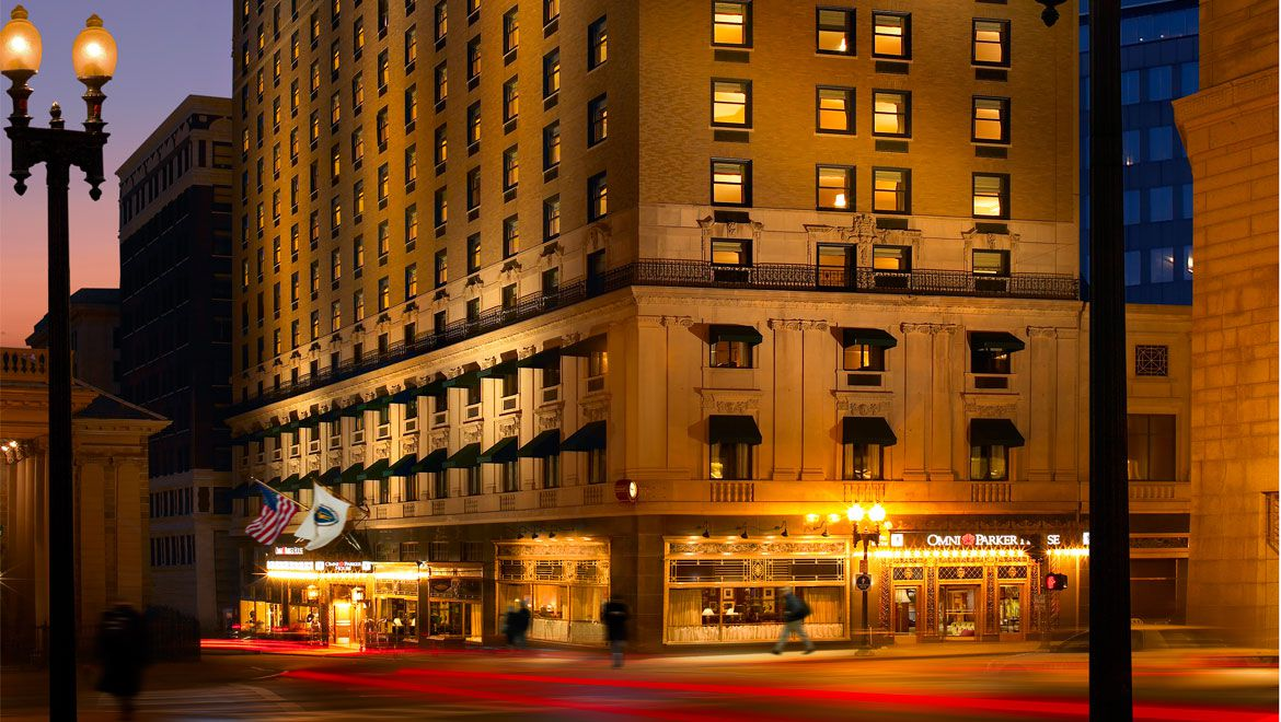 The exterior of the Omni Parker House at night. The facade is tan and there are multiple windows. There is a street lamp in the foreground.