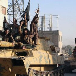 """In this undated file image posted by the Raqqa Media Center, in Islamic State group-held territory, on Monday, June 30, 2014, which has been verified and is consistent with other AP reporting, fighters from the Islamic State group ride tanks during a parade in Raqqa, Syria. A major battle to liberate the northern Syrian city of Raqqa from Islamic State militants is looming, with U.S. officials looking to build on momentum from the battlefields in Mosul. Armed with a new Pentagon plan to """"rapidly defeat"""" the militants in both countries, President Donald Trump is now mulling options for upping the fight, which a top U.S. commander says he expects to be concluded within six months. (Raqqa Media Center via AP, File)"""