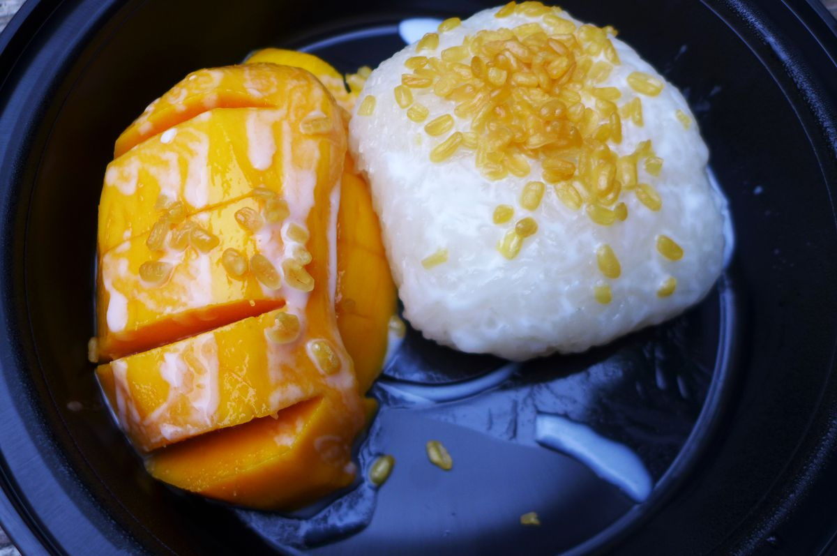 A peeled mango and a lump of coconut soaked rice.