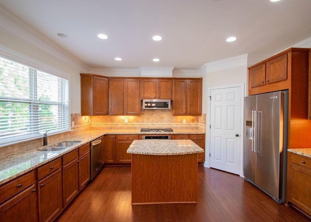 Large kitchen with island, wood cabinets, stainless  appliances, and light countertops.